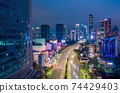 Aerial night view of fast moving traffic on the multi lane highway through urban city center with skyscrapers Highway through downtown Jakarta, Indonesia 74429403