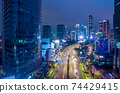 Aerial night view of the traffic on the multi lane highway through modern city center with skyscrapers Downtown Jakarta urban city center 74429415