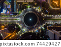 Top down overhead aerial view of moving car traffic at roundabout Vehicle road traffic around Selamat Datang monument in Jakarta, Indonesia at night 74429427