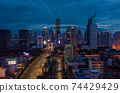 Night aerial wide view of skyscrapers and multi lane highway in large urban city center Cityscape of high rise buildings in Jakarta, Indonesia at night 74429429
