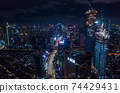Aerial night view of high rise skyscrapers under construction and modern city center with multi lane highway in Jakarta, Indonesia 74429431