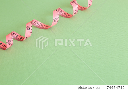Pink tape measure on green background 74434712