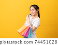 woman holding multi coloured shopping bags and credit card on orange background. 74451029