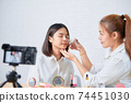woman beauty vlogger video online is showing make up on cosmetics products and live video on camera. 74451030