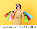 woman casual clothes holding multi coloured shopping bags on light yellow background. 74451038