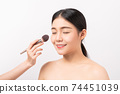 Beauty shot of woman with hand holding makeup powder brush on face. Cosmetic of perfect skin. 74451039