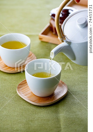 Cups of green tea and teapot. 74455731