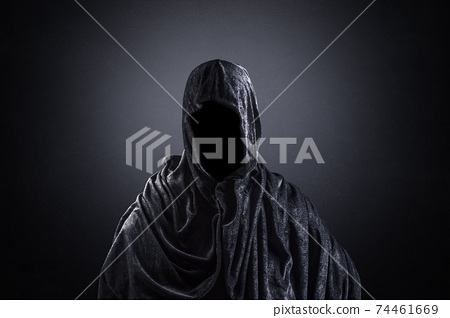Scary figure with hooded cape in the dark 74461669
