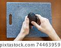 A man peeling an avocado 74463959