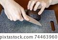 A man peeling an avocado 74463960