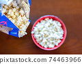 Pouring the popcorn into a dish 74463966
