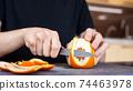 A man peeling an orange 74463978