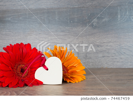 big red and orange flowers with heart shape on rustic wooden background 74467459