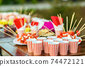 Table with colored sweet snacks. Outdoor party 74472121