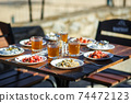 Plates with food on a wooden table on a summer terrace in a cafe 74472123