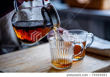 Woman is making hot tea in the kitchen. 74494091