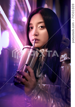 Young adult trendy woman in glowing neon light drinking beverage 74501809
