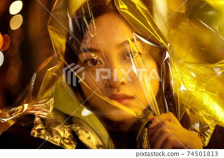 Teenager hipster girl with polyethylene film on head in vibrant neon light 74501813