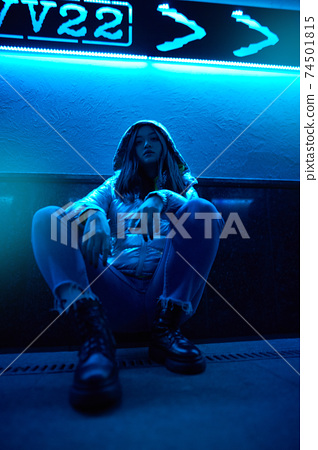 Young adult hipster woman sitting under glowing neon light 74501815