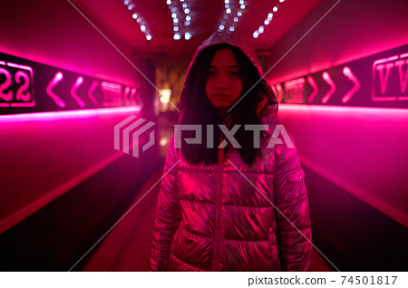 Neon Style. Asian girl in glossy jacket standing in the corridor with fluorescent pink lights looking camera confident 74501817