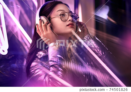 Neon Style. Asian girl in glossy jacket eyeglasses and headphones standing on the street in fluorescent violet lights listening to music looking up smiling joyful 74501826