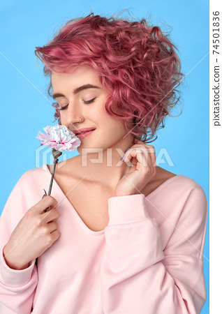 Smiling girl with pink curly hair and nose piercing sniffing carnation flower and enjoying fragrance 74501836