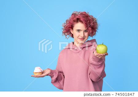 Girl in hoodie preferring fresh green apple to sweet cupcake 74501847