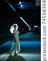 一個半女人站在凱恩斯站內的一把傘 74508368