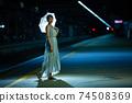 一個半女人站在凱恩斯站內的一把傘 74508369