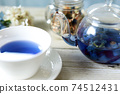 Butterfly pea blue herbal tea in a glass teapot and teacup 74512431
