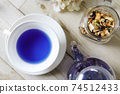 Butterfly pea blue herbal tea in a glass teapot and teacup 74512433