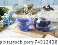 Butterfly pea blue herbal tea in a glass teapot and cup 74512438