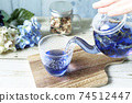 Pour butterfly pea blue herbal tea from a glass teapot into a cup 74512447