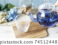 Pour butterfly pea blue herbal tea from a glass teapot into a cup 74512448