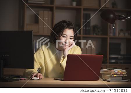 便攜式計算機上工作的年輕女子的夜間圖像 74512851