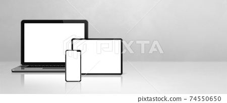 Laptop, mobile phone and digital tablet pc on white concrete office desk. Banner background 74550650
