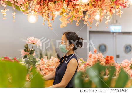 Woman in medicail mask chooses artificial flowers in flower shop. 74551930