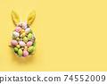 Colorful pastel easter eggs in plate and bunny ears on yellow. Easter greeting card. 74552009