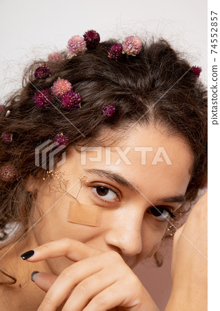Girl with flowers on cheek smiling and looking at the camera 74552857
