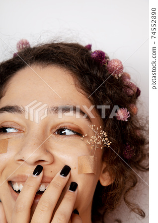 Girl with curly hair and wildflowers under her eyes 74552890