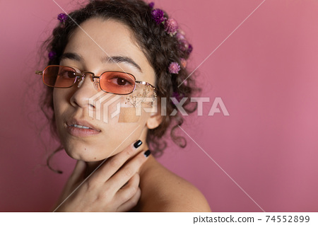 Girl with flowers on her face looking at the camera 74552899