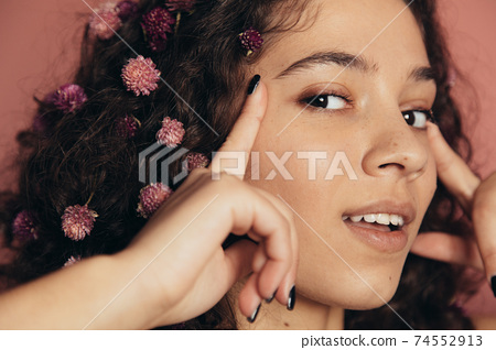 Female with curly hair touching temples with her fingers 74552913