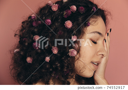 Curly woman closed her face with her hand and posing 74552917