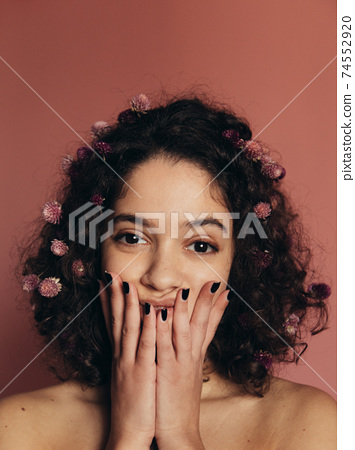 Girl closing mouth with her hands and looking at camera 74552920