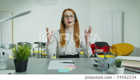 Young business woman receptionist wear headphone video conference calling and talk by webcam in online chat, customer support service and online study teaching concept. 74562234