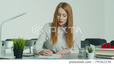 Young redhead woman in glasses has online business conference call. nods, listens, keeps silent, smiles. Webcam view. Education concept. Quarantine concept. Study by internet. 74562236