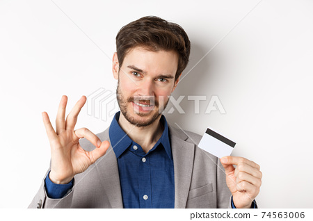 Shopping. Handsome man showing okay sign and plastic credit card, all under control, no worries gesture, white background 74563006