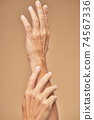 Photo of beautiful female hands on a beige background 74567336