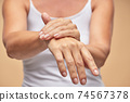 Woman in white t-shirt using hand skin care product 74567378