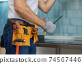 Expert. Cropped shot of young repairman, professional plumber holding a screwdriver while fixing a sink in the kitchen indoors 74567446